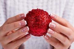 Dziewczyny mienia Bożenarodzeniowa piłka w palcach zdjęcie royalty free