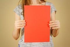 Dziewczyny mienia czerwieni A4 pusty papier pionowo Ulotki prezentacja Zdjęcia Stock