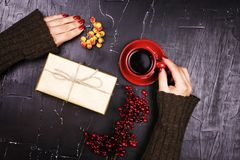 Dziewczyny mienia czerwona filiżanka kawy na ciemnym tle Zdjęcia Royalty Free