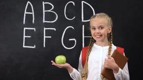 Dziewczyny mienia jabłczany pobliski chalkboard, zdrowy przekąszać dla dzieciaków, abecadło pisać zbiory