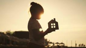 Dziewczyny mienia papieru dom na plaży podczas zmierzchu Ludzie, sen, rodzina, nieruchomość i domowy pojęcie, Dziecko sen zbiory wideo