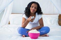 Dziewczyny mienia pilot do tv podczas gdy oglądający telewizję Fotografia Royalty Free