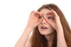 Dziewczyny mienia ręki przy jej oczami jak lornetki zdjęcia royalty free