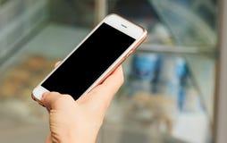 Dziewczyny mienia smartphone, latarnia uliczna jest dniem, zamazany tło obrazy royalty free