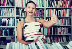 Dziewczyny mienia sterta książek przedstawienia wali up w bookstore Zdjęcia Stock