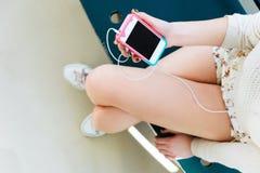 Dziewczyny mienia telefon komórkowy z hełmofonami Fotografia Stock