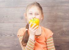 dziewczyny mienia warzywa na drewnianym tle Obrazy Stock
