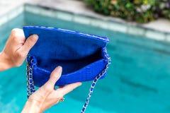 Dziewczyny mienie otwierał luksusową snakeskin pytonu torebkę na pływackiego basenu tle Tropikalna wyspa Bali Fotografia Stock