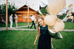 Dziewczyny mienie szybko się zwiększać w plenerowym amerykanin afrykańskiego pochodzenia balonów piękny urodzinowy tort świętuje  Obraz Stock