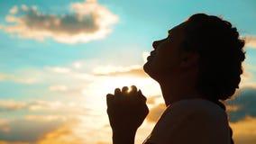 dziewczyny modlenie dziewczyna składał jej ręki w modlitewnej sylwetce przy zmierzchem zwolnionego tempa wideo Dziewczyna styl ży zdjęcie wideo