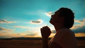 dziewczyny modlenie dziewczyna składał jej ręki w modlitewnej sylwetce przy zmierzchem zwolnionego tempa wideo Dziewczyna składał zbiory