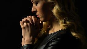 Dziewczyny modlenie odizolowywający na czerni, światło spada na twarzy jak znaka przebaczenie zbiory