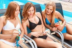 Dziewczyny na bryczki longue pobliskim basenie obrazy stock