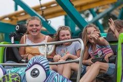 Dziewczyny na karnawałowej przejażdżce przy stanu jarmarkiem Obrazy Royalty Free