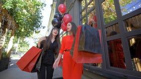 Dziewczyny na zakupy, kobieta przyjaciele komunikują po buyin w drogim przechują w sezonie rabaty przy czarnym Piątkiem zbiory