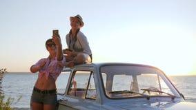 Dziewczyny Nagrywają wideo na telefonie komórkowym blisko pojazdu sunąć rzekę, młode dziewczyny z maszyną Fotografującą smartphon zbiory wideo