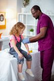 Dziewczyny obsiadania spokój podczas gdy pediatra robi zastrzykowi dla ona zdjęcia royalty free