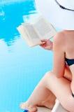 Dziewczyny obsiadanie blisko basenu z książką w ręce Obrazy Royalty Free