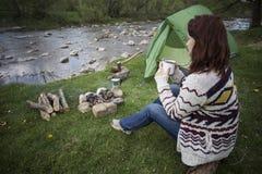 Dziewczyny obsiadanie blisko ogniska przy campsite patrzeje mapę i pije kawę Obraz Stock
