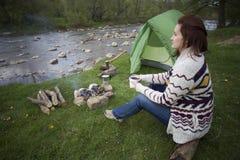 Dziewczyny obsiadanie blisko ogniska przy campsite patrzeje mapę i pije kawę Zdjęcia Stock