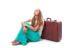 Dziewczyny obsiadanie blisko walizki, odizolowywającej na bielu obraz royalty free