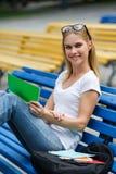 Dziewczyny obsiadanie na ławki mienia pastylce fotografia stock
