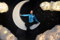 Dziewczyny obsiadanie na chmurach i księżyc Zdjęcia Stock