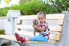 Dziewczyny obsiadanie na cuddling małpy zabawce i ławce obraz stock