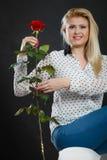 Dziewczyny obsiadanie na kanapie trzyma czerwieni róży na zmroku, Obraz Royalty Free