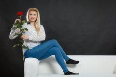 Dziewczyny obsiadanie na kanapie trzyma czerwieni róży na zmroku, Obrazy Stock