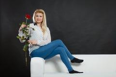 Dziewczyny obsiadanie na kanapie trzyma czerwieni róży na zmroku, Zdjęcia Stock