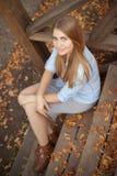 Dziewczyny obsiadanie na krokach drewniany ganeczek, jesień sezon fotografia stock