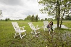 Dziewczyny obsiadanie na krześle w deszczu Rozchlupotanym jardzie obraz stock