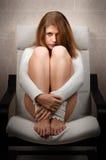 Dziewczyny obsiadanie na krześle w pokoju Zdjęcia Stock