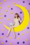 Dziewczyny obsiadanie na księżyc zabawce Fotografia Stock