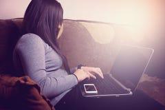 Dziewczyny obsiadanie na leżance i działanie z laptopem Zdjęcie Royalty Free