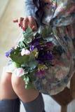 Dziewczyny obsiadanie na mieniu i krześle bukiet kwiaty w ona Fotografia Royalty Free