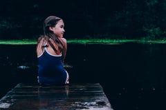 Dziewczyny obsiadanie na molu przyglądającym z powrotem zdjęcie royalty free