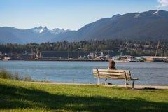 Dziewczyny obsiadanie na parkowej ławce w Vancouver z lwami w tle fotografia royalty free