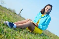 Dziewczyny obsiadanie na polu w lecie zdjęcie stock