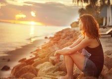 Dziewczyny obsiadanie na skałach na dopatrywaniu i plaży zmierzch Obraz Stock