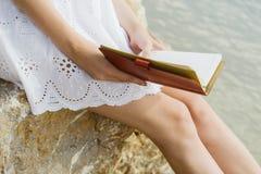 Dziewczyny obsiadanie na skałach morzem, pracuje z laptopem Fotografia Royalty Free