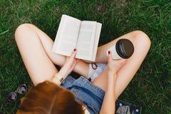 Dziewczyny obsiadanie na trawie z filiżanką kawy Obraz Royalty Free