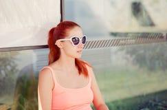 Dziewczyny obsiadanie przy autobusową przerwą w okularach przeciwsłonecznych czeka autobus obraz royalty free