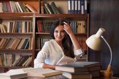 Dziewczyny obsiadanie przy stołowym czytaniem książka przygotowywa dla egzaminu obrazy royalty free
