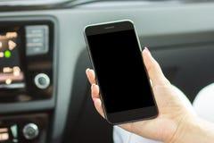 Dziewczyny obsiadanie w samochodowym mieniu smartphone w jej ręce, zakończenie zdjęcia royalty free