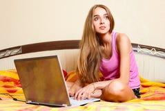 Dziewczyny obsiadanie w sypialni na łóżku z laptopem Zdjęcia Stock