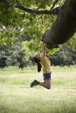 Dziewczyny obwieszenie Od gałąź Zdjęcie Stock