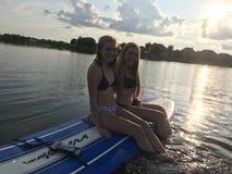 Dziewczyny paddle abordaż na jeziorze zdjęcia royalty free