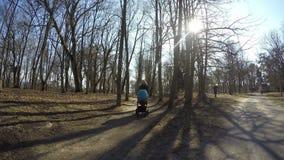 Dziewczyny pchnięcia błękitnego dziecka fracht w wiosna parka drzewa alei 4K zdjęcie wideo